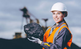Coal mining worker. Worker with piece of coal in her hand at an open pit Stock Photo