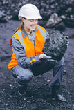 Coal mining worker. Worker with piece of coal in her hand at an open pit Stock Image