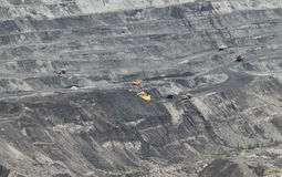 Coal open-pit. Excavator in coal mine and yellow truck Stock Photo