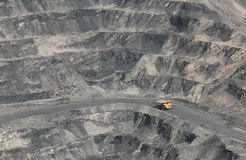 Coal open-pit. Excavator in coal mine and yellow truck Royalty Free Stock Image