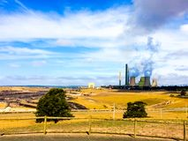 Coal power electricity plant emitting gas smoke to the cloudy blue sky