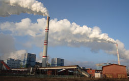 Coal power plant. Polluting the planet, several thin and several thick chimneys smoking towards the sky Stock Image