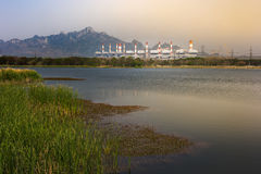 Coal power plant encircled with lake and mountain Stock Photography