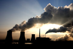 Coal power plant fumes. View of coal powerplant against sun with several chimneys and huge fumes stock images