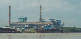 Coal power plant on riverbank with barge full of coal in the dock. Indonesia royalty free stock image
