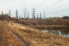 Coal power station in beautiful area full of trees and lake, mirror reflection of energetic pole and power station with chimneys,. Synergy of industry and stock image