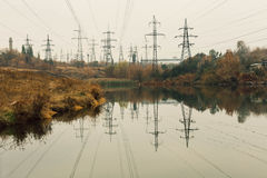 Coal power station in beautiful area full of trees and lake, mirror reflection of energetic pole and power station with chimneys,. Synergy of industry and Stock Images