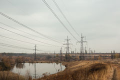Coal power station in beautiful area full of trees and lake, mirror reflection of energetic pole and power station with chimneys,. Synergy of industry and royalty free stock image