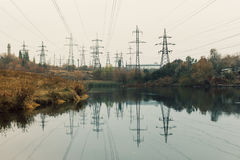 Coal power station in beautiful area full of trees and lake, mirror reflection of energetic pole and power station with chimneys,. Coal power station in the stock images