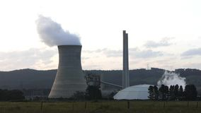 Coal power station. Steaming cooling towers of a coal fired power station. Filmed on a warm summers evening stock footage