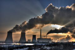 Coal powerplant view - chimneys and fumes. View of coal powerplant against sun with several chimneys and huge fumes stock photos