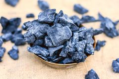 Coal in a rusted bowl on a gunny background. Concept of beauty and health Stock Photos