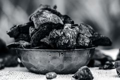 Coal in a rusted bowl on a gunny background. Concept of beauty and health Royalty Free Stock Images