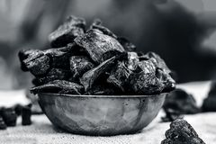 Coal in a rusted bowl on a gunny background. Concept of beauty and health Stock Photography