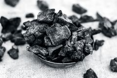 Coal in a rusted bowl on a gunny background. Concept of beauty and health Stock Photo