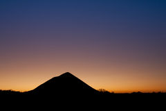 Coal tip over sunset. Shadow of a coal tip over a sunset in the blue hour stock photography