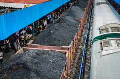 Coal Train - India. Coal train waiting at station in India, people waiting for a passenger train Stock Image