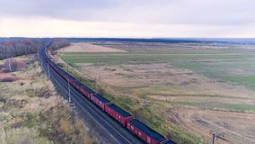 A coal train moves along the double tracks. A long freight train loaded with coal moves away from the camera stock video