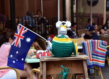 A coala de Knitten que senta-se em um amarelo e verde knitten o bule confortável Fotografia de Stock Royalty Free