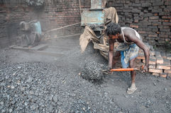 Coalman. An worker pouring coal in a machine in a dusty environment Royalty Free Stock Image