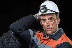 Coalminer holds out a large chunk of energy rich. A coalminer holds out a large chunk of energy rich coal in a dark coalmine stock photo