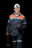 Coalminer holds out a large chunk of energy rich. A coalminer holds out a large chunk of energy rich coal in a dark coalmine stock photos