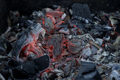 Coals on fire in ashes Stock Photos