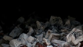 Coals in the furnace. Smoldering firewood background. Burnt firewood. Heat for cooking. Ashes rises. Selective focus change.