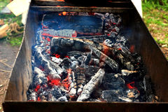 The coals in the grill. Burning charcoal in the background in barbecue Stock Images
