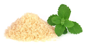 Coarse crystals of brown sugar with stevia leaves Royalty Free Stock Photo