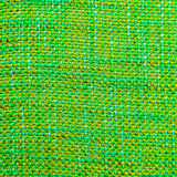 Coarse fabric background. Close up of coarse fabric woven from different colored threads in golden and green Royalty Free Stock Image