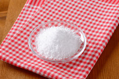 Coarse grained edible salt. On small glass plate Stock Photography