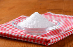 Coarse grained edible salt. On small glass plate Royalty Free Stock Image