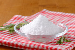 Coarse grained edible salt. On small glass plate royalty free stock images