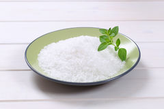 Coarse grained salt. Plate of coarse grained sea salt on white wooden background royalty free stock photo