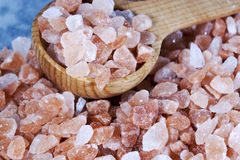 Coarse Himalayan Pink Salt Spoon. Coarse Himalayan pink salt in wood spoon and scattered on blue grey marble surface, Pink salt gets its color from iron and stock images