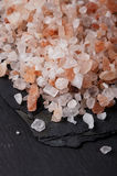 Coarse pink himalayan, sea salt on black slate Stock Images