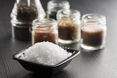 Coarse salt. Black bowl with coarse salt with variety of salt on black table royalty free stock photo