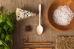 Coarse salt in the old wooden plate, white mold cheese, almonds, cinnamon sticks, mint on old flax tablecloths Royalty Free Stock Photos