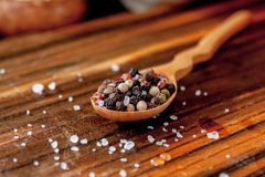 Coarse salt and pepper in a wooden spoon. Coarse salt and pepper in a wooden spoon Royalty Free Stock Photo