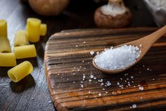 Coarse sea salt. In wooden spoon over kitchen board royalty free stock image