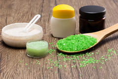 Coarse sea salt with natural scrubs and skin care creams. Close-up of wooden spoon filled with green coarse sea salt, natural scrubs and skin care creams on stock photo