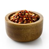 Coarsely ground chilli peppers in dark wood bowl. Stock Images