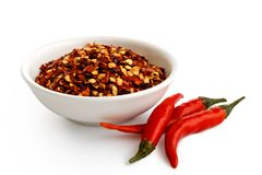 Coarsely ground chilli peppers in white ceramic bowl isolated on. White. Fresh chillies royalty free stock image
