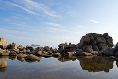 Coast. Granite stones are reflected in water Stock Images