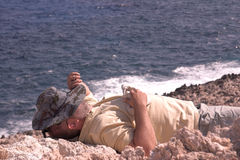 Coast. Resting men at cost of crete Royalty Free Stock Photography