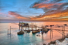 Coast of the Adriatic sea in Chieti, Abruzzo, Italy. Old fishing hut trabocco, the typical wooden palafitte in the sunrise of the Mediterranean sea coast in Stock Image