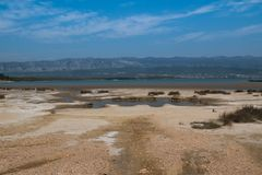 Coast of Adriatic sea, island Krk, Croatia. Sandy beach at the coast of the Adriatic sea. Puddles from the high tide and some dry grass. Mountain on the other stock photography