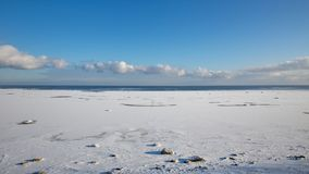 The coast of Baltic sea. Landscape landscape of the Baltic Sea coast in winter with beautiful clouds and blue sky on a sunny day, water and stones, covered with Royalty Free Stock Photography