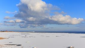 The coast of Baltic sea. Landscape landscape of the Baltic Sea coast in winter with beautiful clouds and blue sky on a sunny day, water and stones, covered with Royalty Free Stock Image
